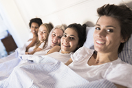 Portrait of smiling female friends lying in bed side by side - GIOF03433