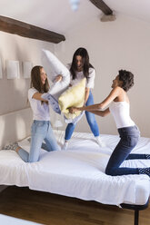 Playful female friends having a pillow fight in bed - GIOF03442
