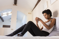 Young woman using cell phone in bedroom - GIOF03445