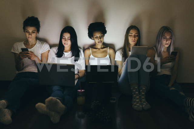 Group of female friends at home sitting on floor using technology in the dark - GIOF03451 - Giorgio Fochesato/Westend61
