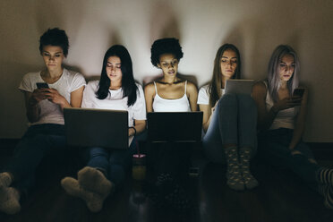 Group of female friends at home sitting on floor using technology in the dark - GIOF03451
