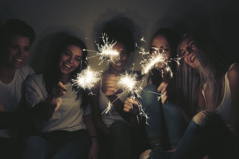 Happy female friends with sparklers in the dark - GIOF03454