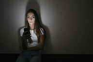 Young woman at home sitting on floor using cell phone in the dark - GIOF03457