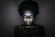 Portrait of young woman using cell phone in the dark - GIOF03460