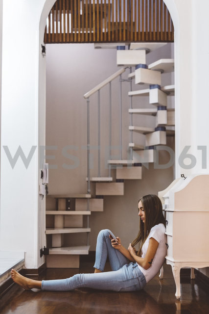 Young woman at home sitting on the floor using cell phone - GIOF03463