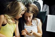 Relaxed mother and daughter with cell phone on sofa - JPF00285