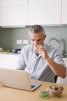 Man drinking water from glass and using laptop in home office - ALBF00255