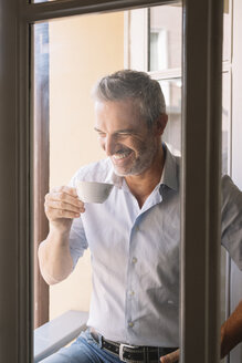 Laughing mature man drinking cup of coffee at the window - ALBF00261