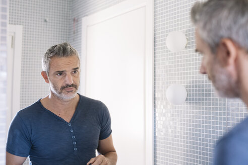 Mature man looking in bathroom mirror - ALBF00267
