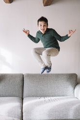 Portrait of boy jumping in the air in the living room - ALBF00289