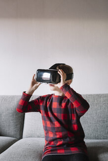 Girl sitting on the couch in the living room using Virtual Reality Glasses - ALBF00307