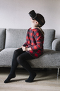Girl sitting on the couch in the living room using Virtual Reality Glasses - ALBF00310