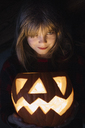 Portrait of smiling girl with lighted Jack O'Lantern at Halloween - ALBF00313