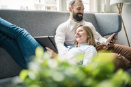Smiling couple using tablet and cell phone on couch - JOSF01908