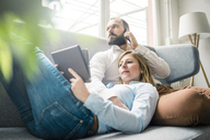 Couple using tablet and cell phone on couch - JOSF01911