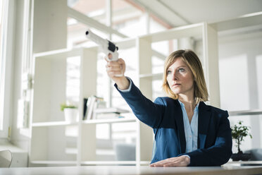 Businesswoman aiming with gun in office - JOSF01923