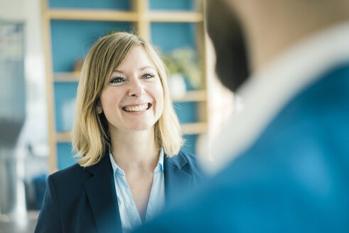 Businesswoman smiling at businessman in office - JOSF01929