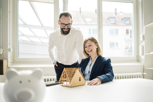 Laughing woman and man with house model and piggy bank  in office - JOSF01932