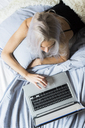 Young woman lying in bed using laptop - GIOF03498
