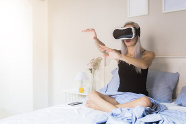 Young woman sitting in bed wearing VR glasses - GIOF03510