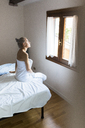 Young woman wrapped in a towel sitting on bed looking out of window - GIOF03519