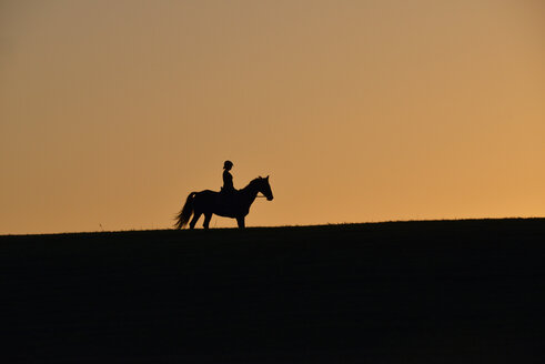 Silhouette of female rider at sunset - GNF01422