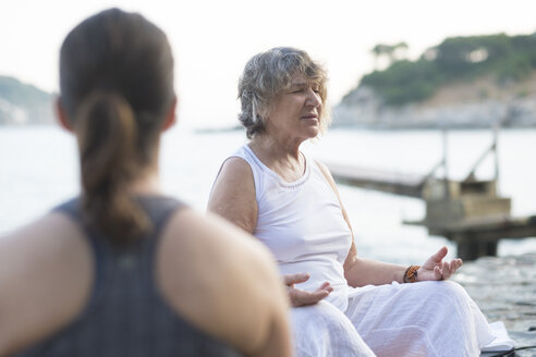 Senior woman doing a yoga exercise at the coast - ABAF02181