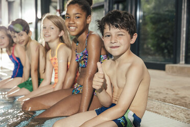 Portrait of smiling children sitting on poolside in indoor swimming pool - MFF04149