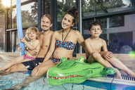 Portrait of happy family sitting on poolside in indoor swimming pool - MFF04152