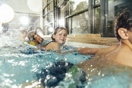 Children in swimming class practicing at poolside in indoor swimming pool - MFF04155