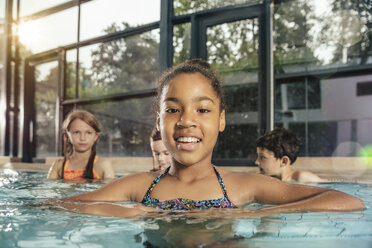 Portrait of smiling girl with friends in indoor swimming pool - MFF04158
