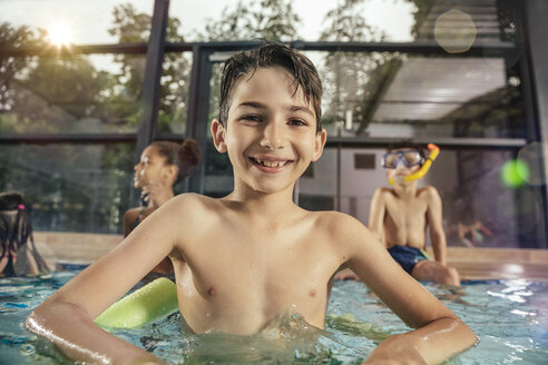 Portrait of smiling boy with friends in indoor swimming pool - MFF04161