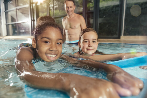 Portrait of smiling girls with instructor practicing in indoor swimming pool - MFF04164