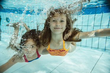 Portrait of two girls swimming under water in swimming pool - MFF04170