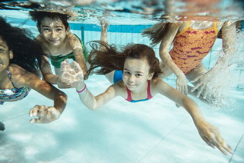 Portrait of happy children swimming under water in swimming pool - MFF04173