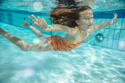 Portrait of smiling girl swimming under water in swimming pool - MFF04176
