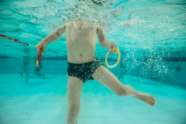 Boy holding two diving rings under water in swimming pool - MFF04182