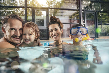 Portrait of happy family with two children in indoor swimming pool - MFF04185