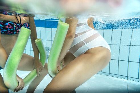 Two pregnant women doing water gymnastics under water in indoor swimming pool - MFF04188