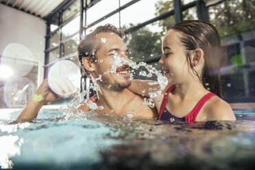 Happy father with daughter splashing in indoor swimming pool - MFF04197