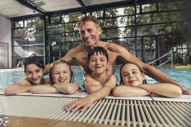 Portrait of smiling children with instructor in indoor swimming pool - MFF04206