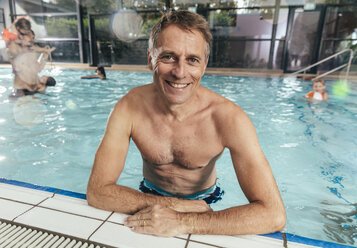 Portrait of smiling man in indoor swimming pool - MFF04209