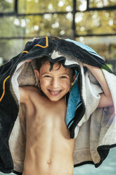 Portrait of happy boy toweling himself at the poolside of an indoor swimming pool - MFF04215