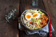 Bowl of glutenfree Udon noodle soup with carrots, Chinese cabbage, zoodles, mungo beans sprouts and boiled egg - SBDF03383