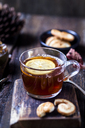 Glass of black tea with slice of lemon and rock sugar on wooden table - SBDF03388