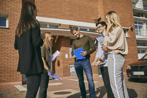 Group of happy students standing outdoors with documents - ZEDF01000