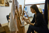 Student painting on easel in art class - ZEDF01009