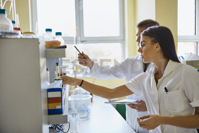 Young man and woman working together in laboratory - ZEDF01012