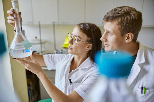 Young man and woman looking at liquid in flask in laboratory - ZEDF01015