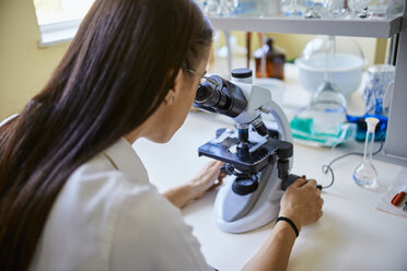 Young woman using microscope in laboratory - ZEDF01018